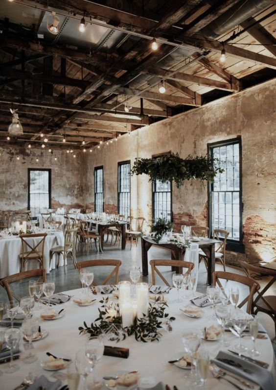 a refined barn wedding tablescape with white linens, a pillar candle and greenery centerpiece and simple glasses