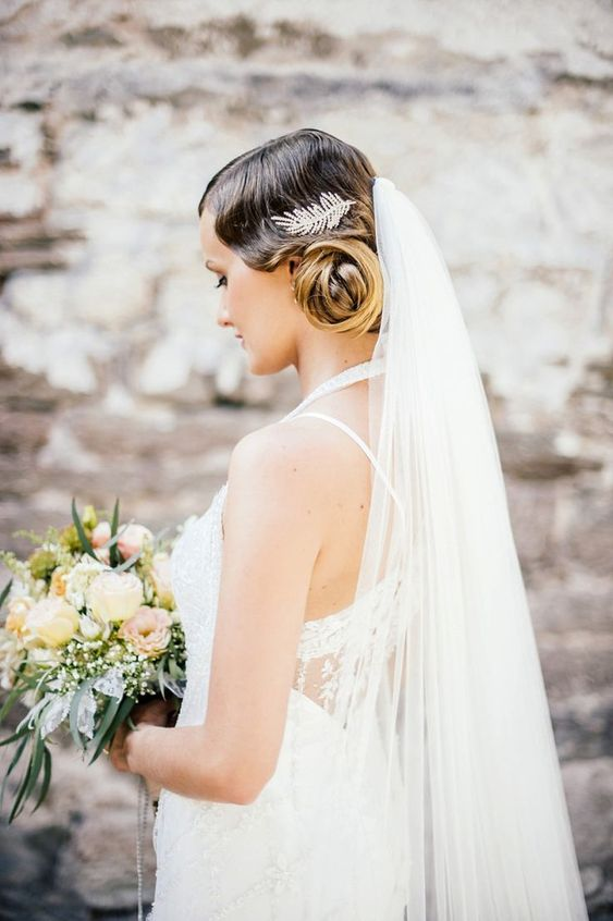 a refined embellished feather hairpiece and a veil will make your bridal look gorgeous and chic