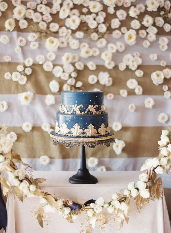 a refined navy and gold wedding cake with patterns