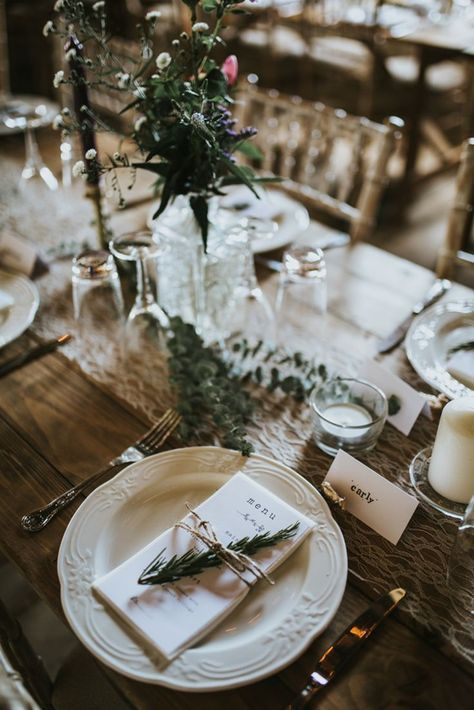 a romantic barn wedding tablescape with a lace runner, a greenery and wildflower centerpiece, white porcelain and touches of fir