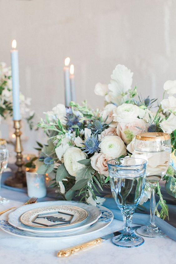 a romantic wedding tablescape with blue candles, glasses and plates plus a neutral floral centerpiece with thistles