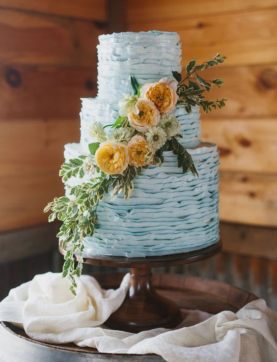 a ruffle powder blue wedding cake decorated with greenery and neutral and rust blooms