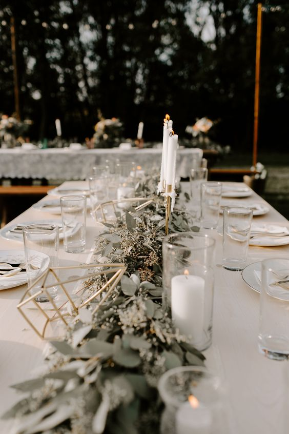a simple barn-like tablescape with a white tablecloth, a lush eucalyptus runner, candles and terrariums