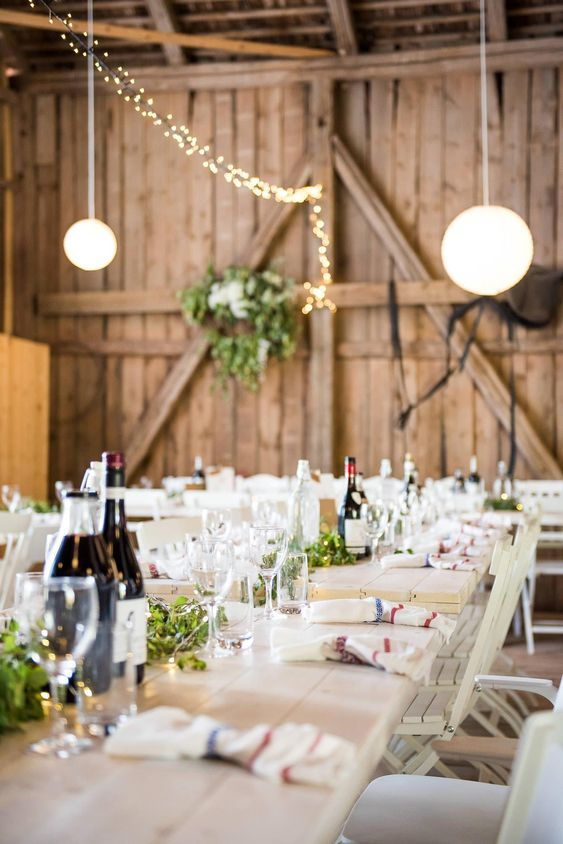 a simple barn wedding table with a greenery and lights runner, bottles and striped napkins