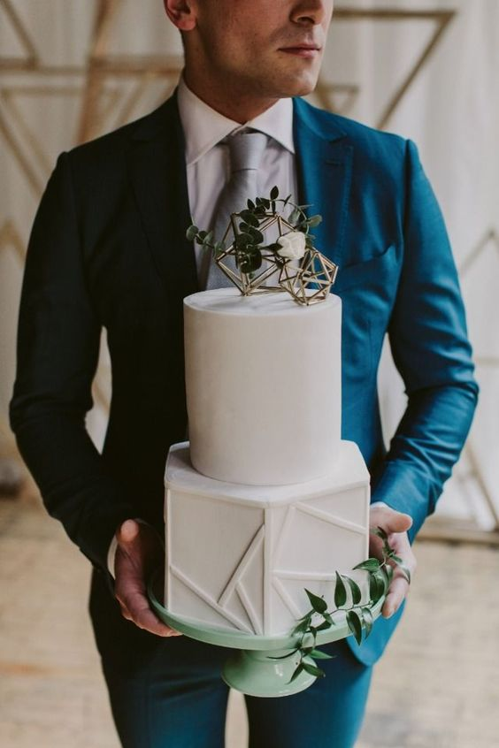 a sophisticated white wedding cake with gold himmeli toppers, greenery and white blooms and 3D geometric patterns is wow