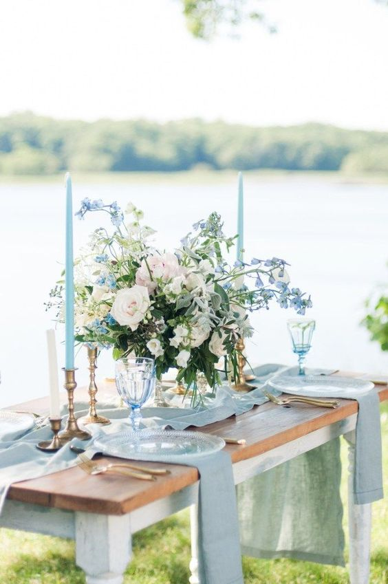a spring wedding tablescape with a runner, napkins, powder blue and white blooms plus powder blue candles