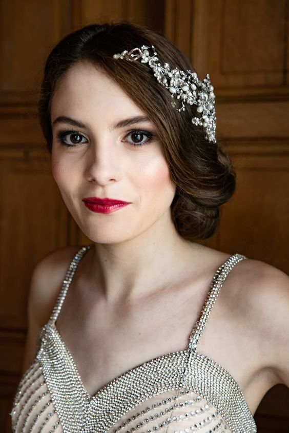 a statement embellished and pearl headpiece highlights the hairstyle and matches the amazing embellished wedding dress