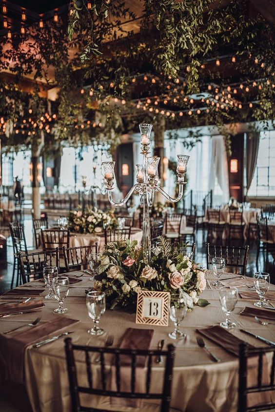 a stylish and chic barn wedding tablescape with neutral linens, a lush blush flower and greenery wedding centerpiece and a crystal candle holder