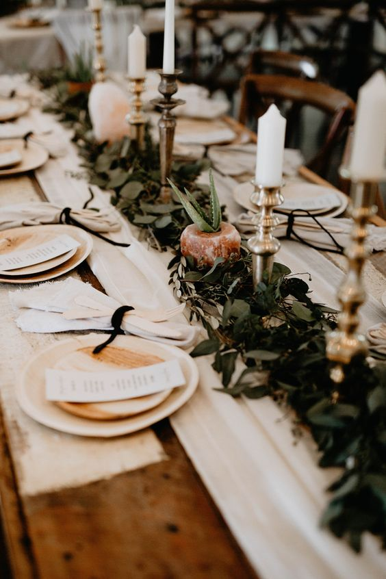 a stylish barn wedding table with a fabric and greenery runner, candles, a succulent and white plates