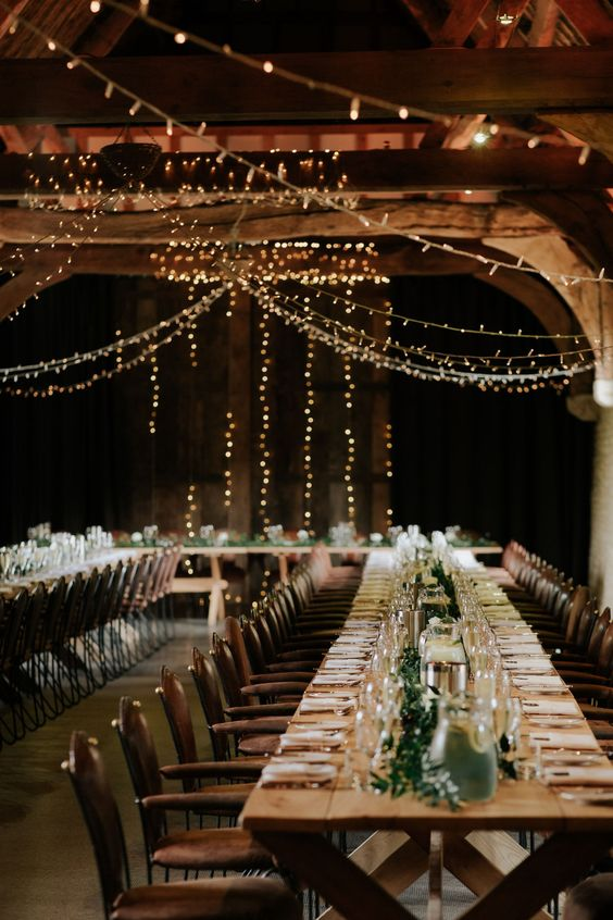 a stylish barn wedding table with a greenery runner, some candles and simpel plates and glasses