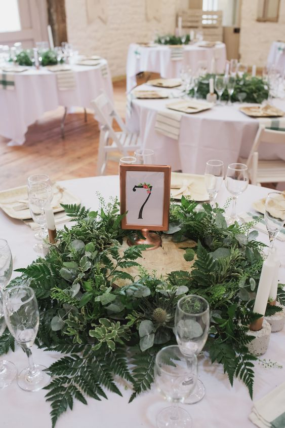 a stylish barn wedding table with white linens, a lush greenery centerpiece and a table number