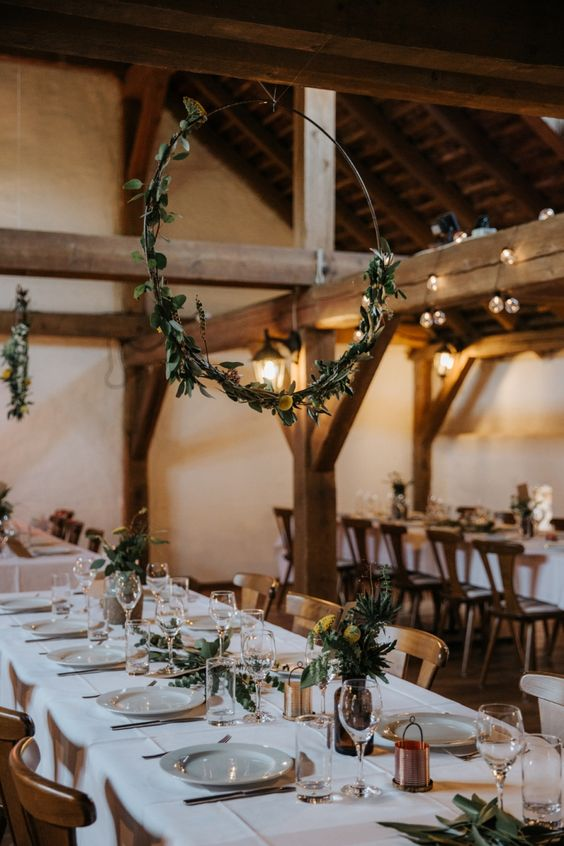 a stylish barn wedding table with white linens, greenery, billy balls, copper touches