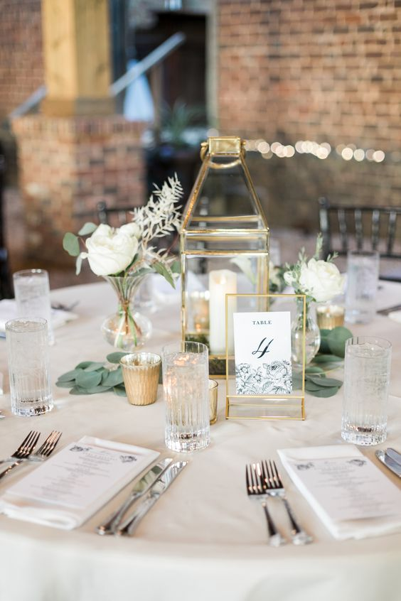a stylish neutral wedding table with a gold candle lantern, a table number, white blooms and greenery and white linens