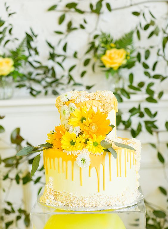 a super bright wedding cake in pale yellow, with bright yellow drip, yellow and rust blooms, greenery and crumbs