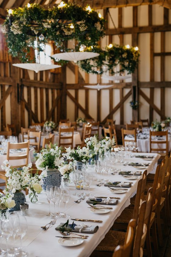 a super elegant barn wedding table with neutral linens, blue vases with white and blue blooms
