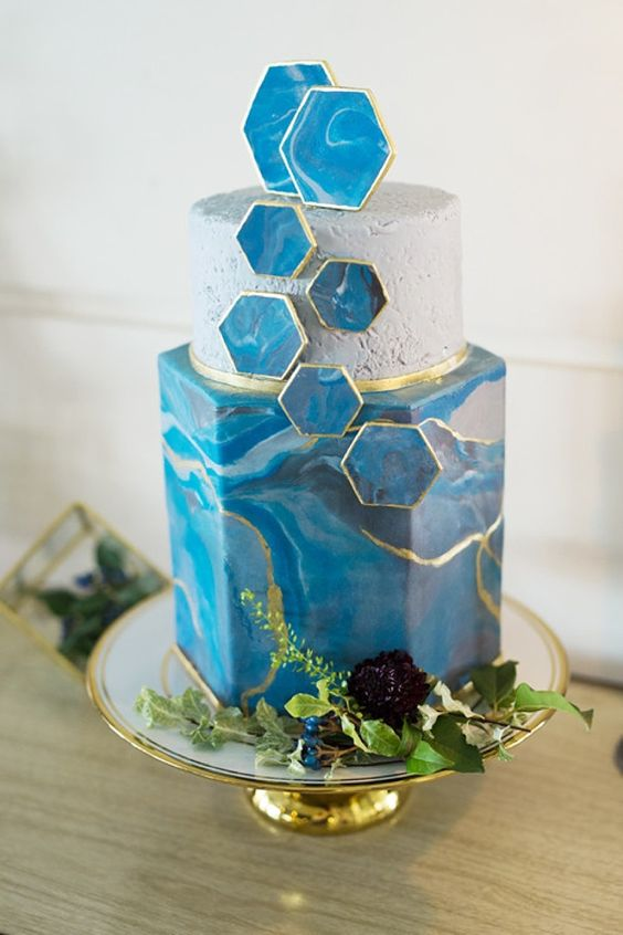 a unique hexagon wedding cake with a white round tier, a blue and gold marble one and blue marble hexaons plus greenery