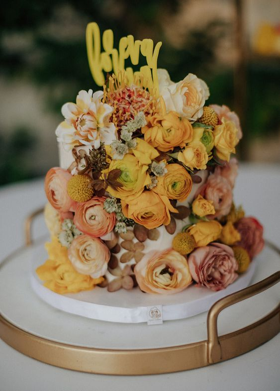 a unique one tier wedding cake with pink, rust, yellow and mustard blooms, dried and fresh, a yellow topper