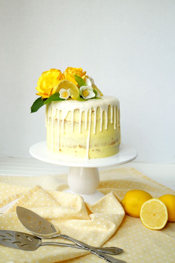 a vegan lemon curd wedding cake with drip and fresh yellow and white blooms and lemons on top