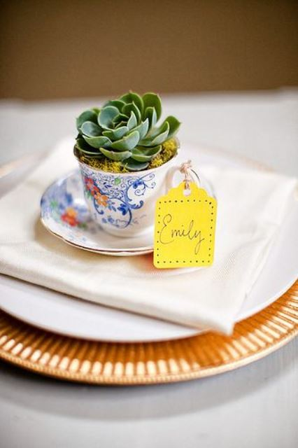 a vintage teacup with a succulent planted and a bright escort card is a fantastic and very eco friendly wedding favor