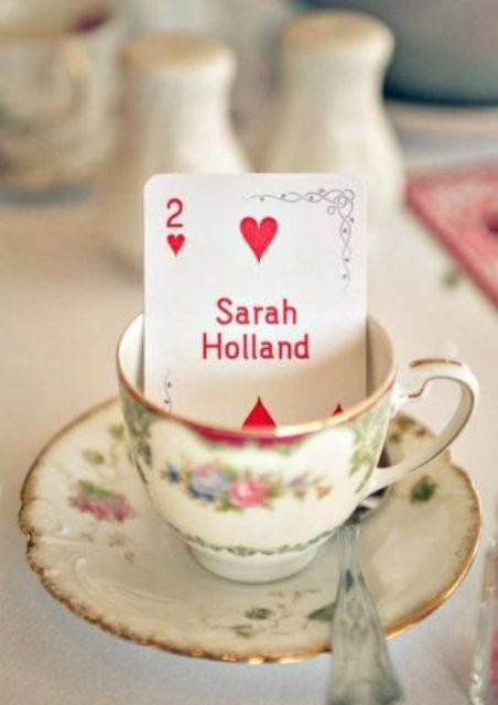 a vintage teacup with an escort card to mark each place setting – great for Alice In Wonderland wedding