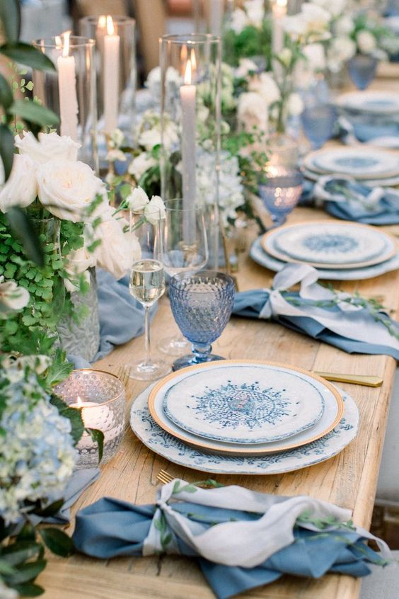 a vivid wedding tablescape with blue glasses, napkins, printed plates and white blooms and greenery plus candles