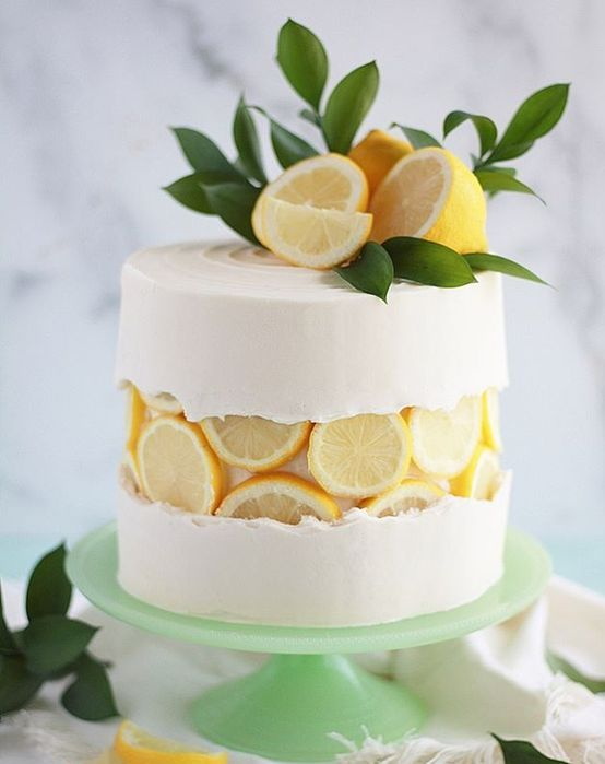 a wedding cake in white with citrus slices, lemons and fresh greenery on top is a cool and yummy-looking idea