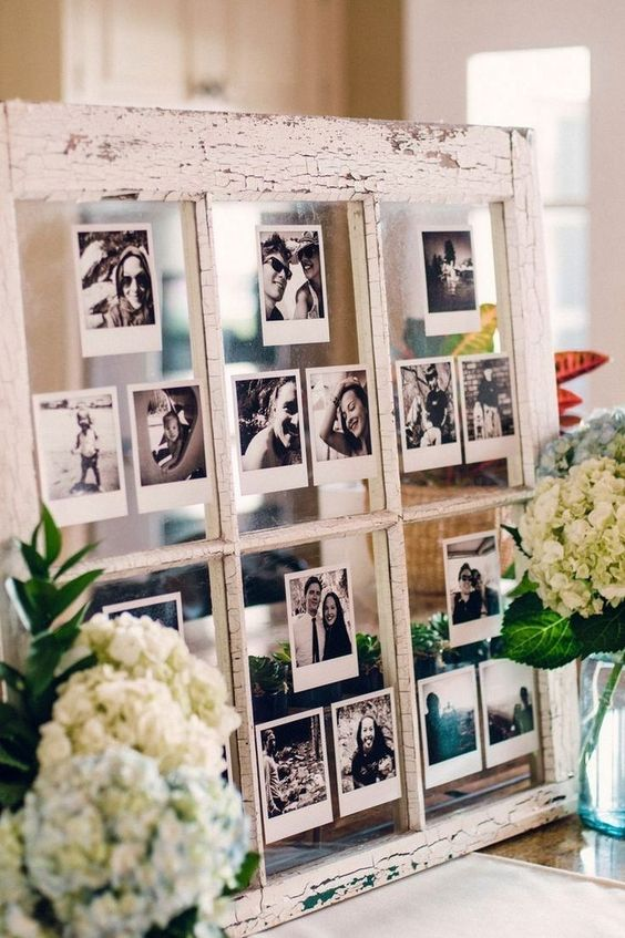 a wedding decoration of a vintage window with black and white Polaroids of the couple