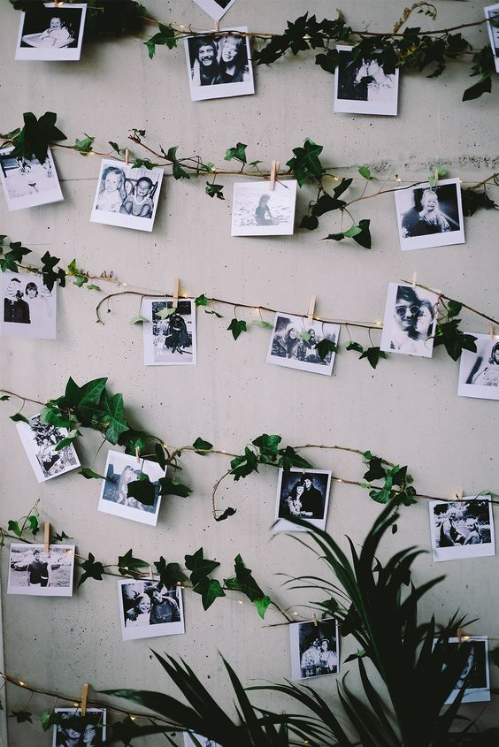 a wedding venue backdrop or just decor with garlands of black and white Polaroids and greenery and lights