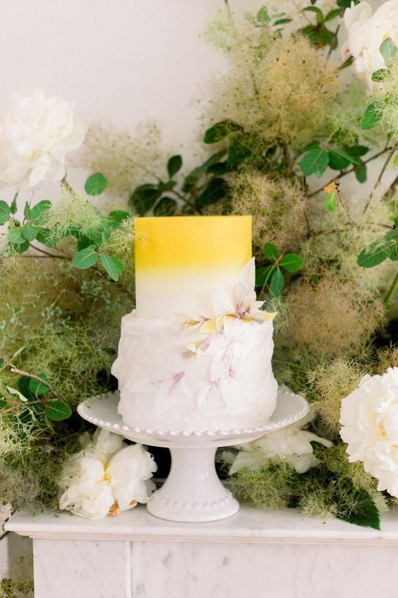 a whimsical yellow to white wedding cake with sugar petals and blooms is a bold and cool idea to rock