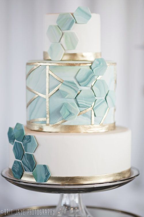 a white and aqua wedding cake with gold decor, with geometric lines, aqua marble hexagons coverign all the tiers looks amazing