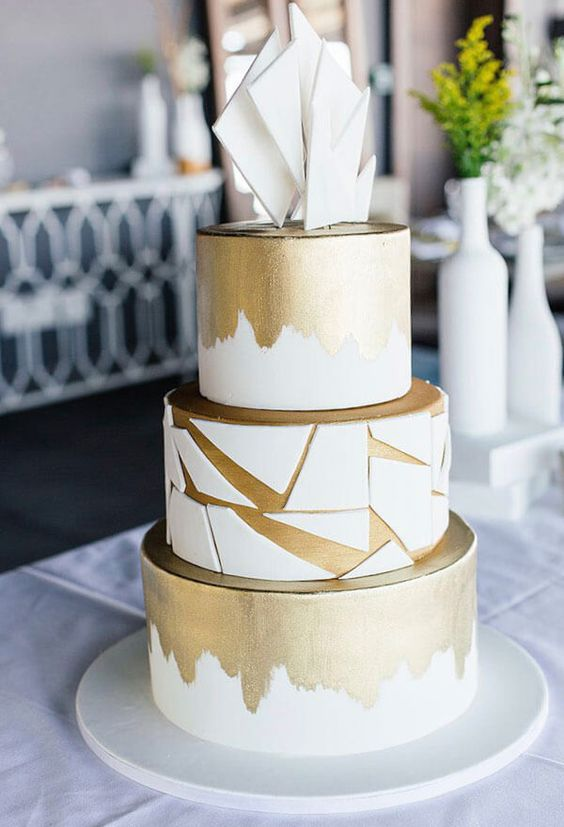 a white and gold wedding cake with brushstrokes and geometric shards plus white shards on top is a very elegant and chic idea