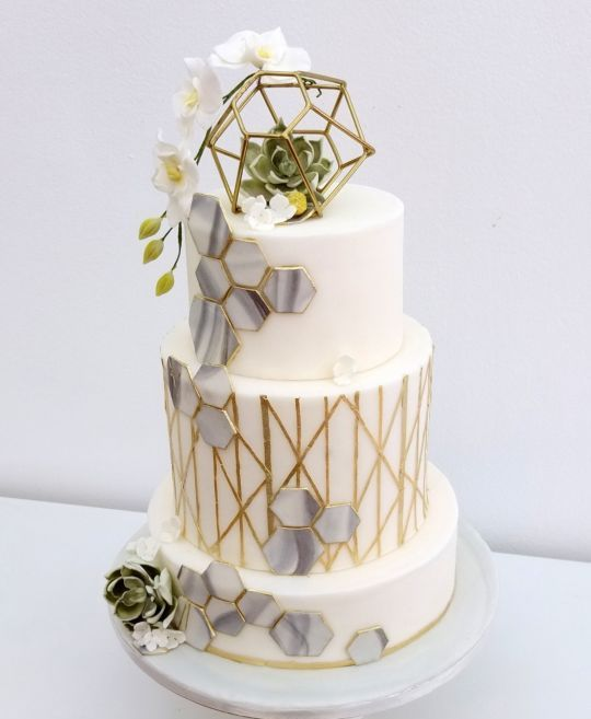 a white and gold wedding cake with grey marble hexagons, gold patterns, a himmeli topper, some white blooms and succulents