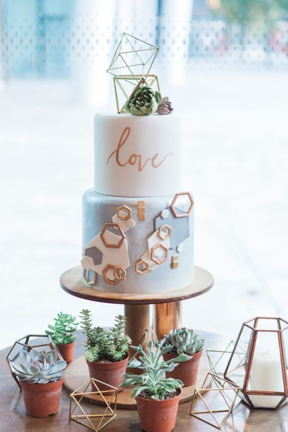 a white and light blue wedding cake with white, blue and copper hexagons, calligraphy and lovely gold himmeli toppers