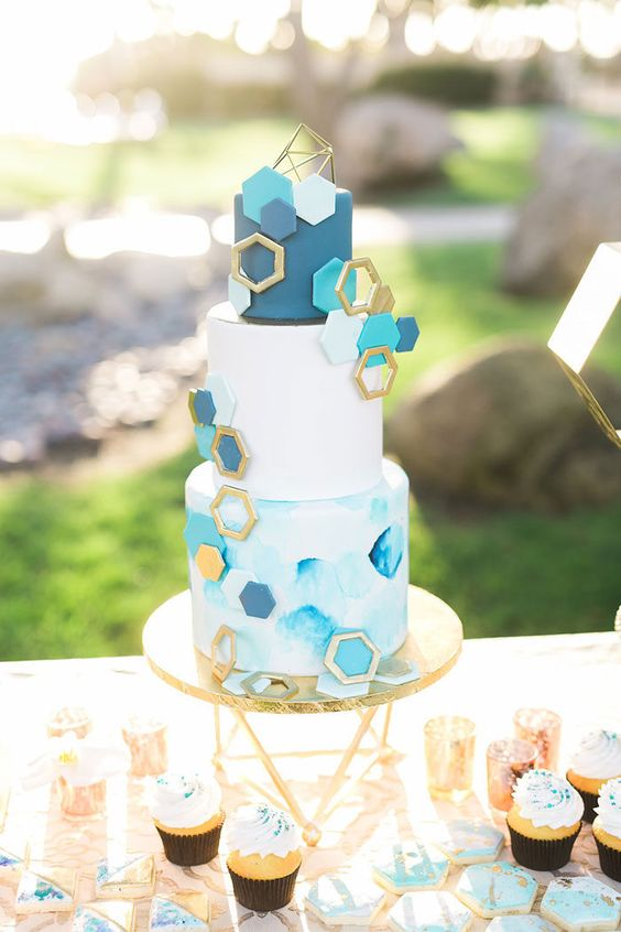 a white, light blue and navy wedding cake with a watercolor tier, a white and a navy one, gold, turquoise and navy hexagons