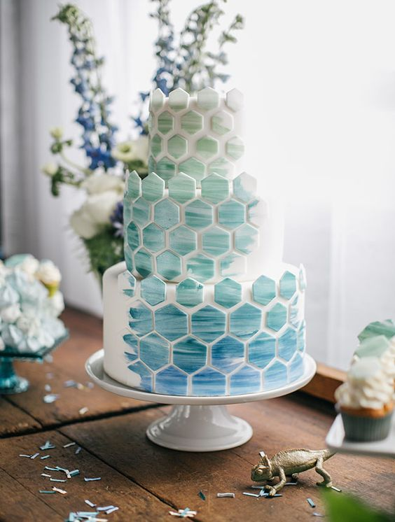 a white round wedding cake with blue and aqua watercolor hexagons covering all the tiers is a very lovely idea