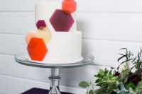 a white round wedding cake with colorful semi sheer hexagons that give a fresh and bold modern feel to it