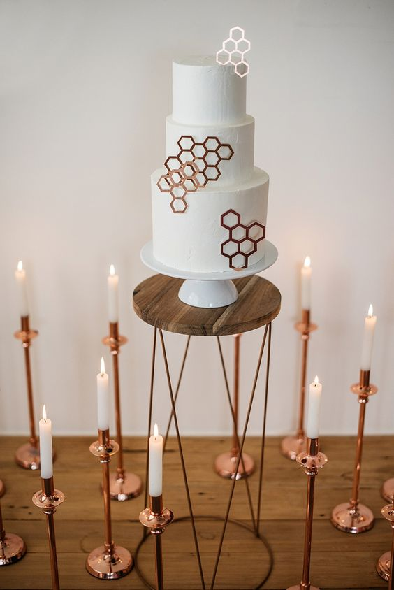 a white round wedding cake with copper hexagons is a stylish and refined idea for a modern wedding with geometric decor