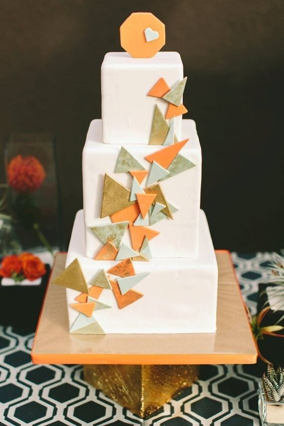 a white square wedding cake with colorful 3D triangles decorating it and an orange topper with a heart is cool and fun
