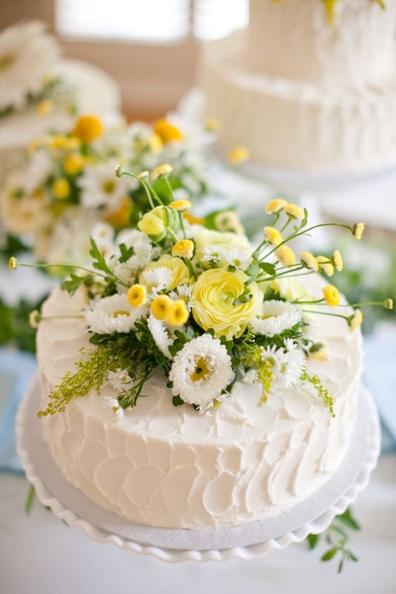 a white textural buttercream wedding cake topped with greenery, white and yellow blooms is a lovely rustic idea for a summer wedding