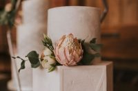 a white textural buttercream wedding cake with white and blush blooms and greenery and with geometric patterns is a lovely idea