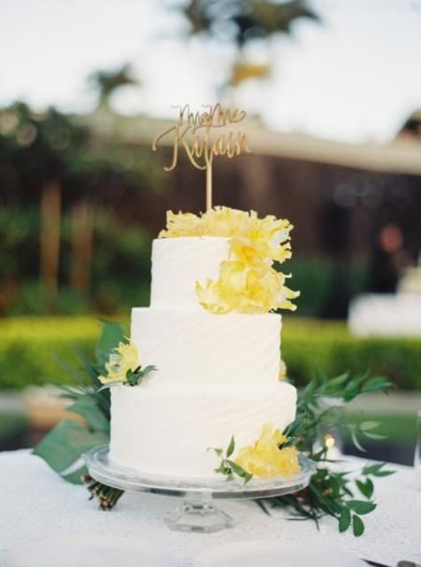 a white textural wedding cake with yellow blooms, greenery and a gold calligraphy topper is all cool