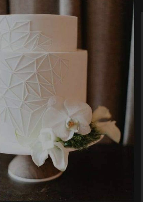 a white wedding cake with geometric decor and white orchids is a stylish idea for a modern wedding