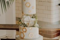 a white wedding cake with gold hexagons and geometric patterns, white orchids and greenery is a chic and refined idea