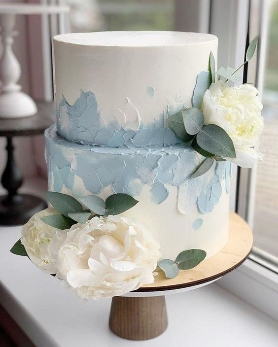 a white wedding cake with powder blue brushstrokes and neutral blooms and leaves