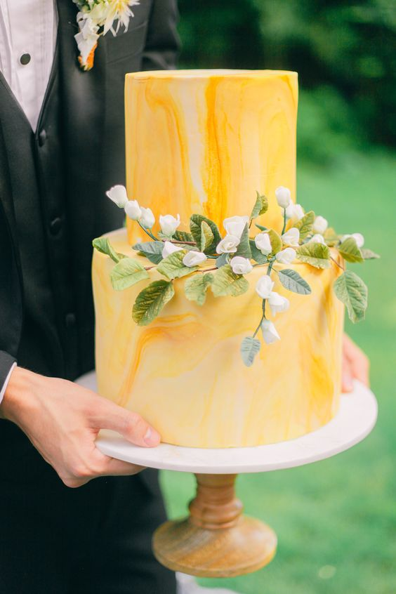 a yellow marble wedding cake with blooms and greenery is a bright and elegant idea for spring or summer