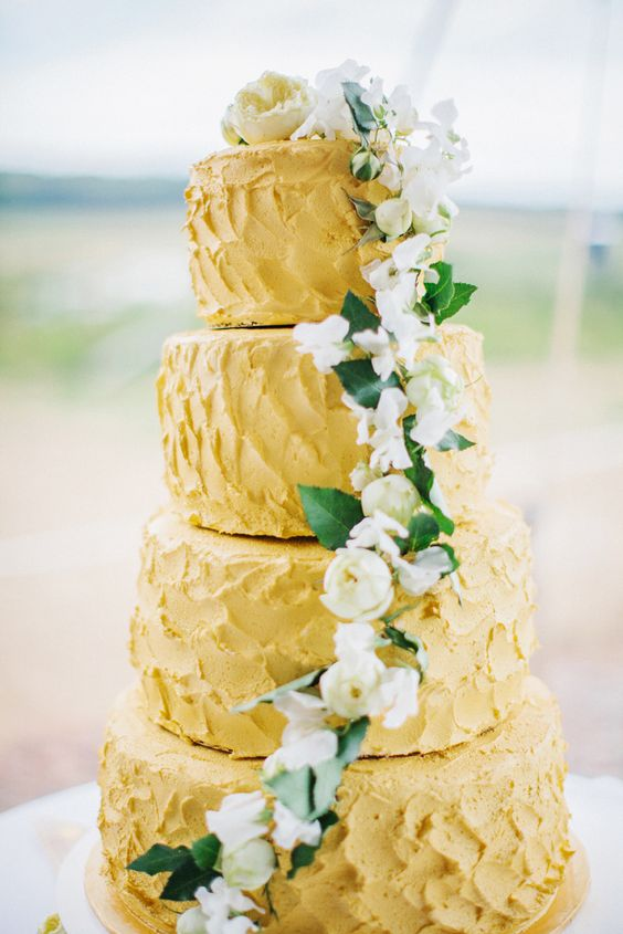 a yellow textural buttercream wedding cake with greenery and neutral blooms is a cool and bold idea for spring