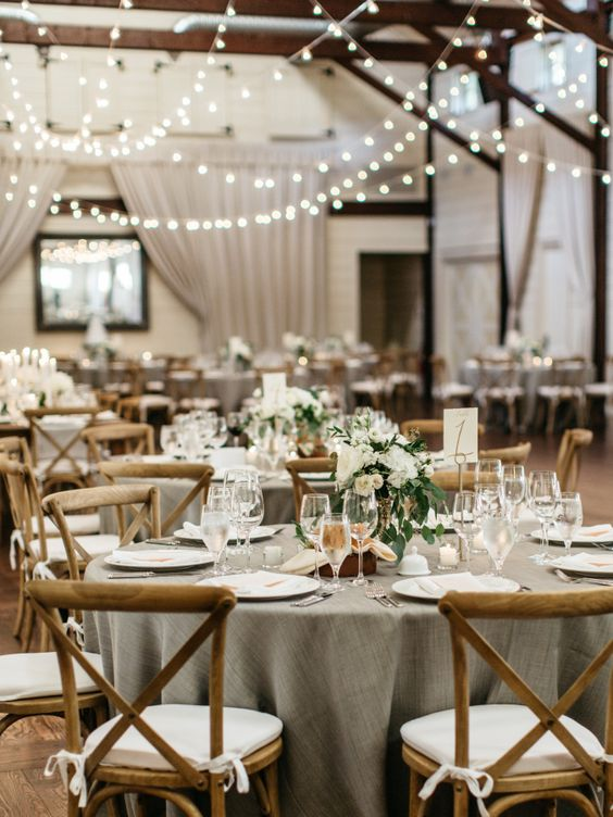 an elegant barn wedding table with a grey tablecloth, white blooms, candles and votives