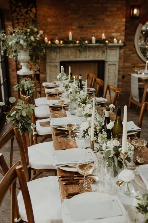 an elegant barn wedding tablescape with an uncovered table, white linens, a greenery and white bloom table runner