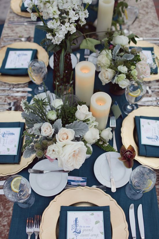an elegant navy blue and gold wedding tablescape with neutral florals, elegant cutlery