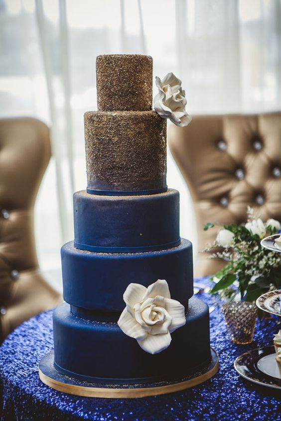 an elegant ombre wedding cake from gold glitter to navy decorated with a single white sugar bloom